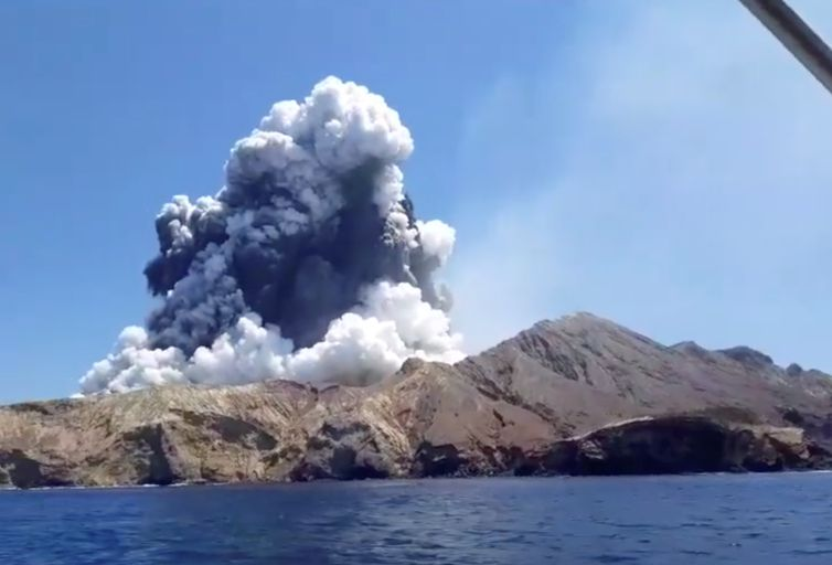 Smoke from the volcanic eruption of Whakaari, also known as White Island, is pictured from a boat, New Zealand December 9, 2019 in this picture grab obtained from a social media video. INSTAGRAM @ALLESSANDROKAUFFMANN/via REUTERS THIS IMAGE HAS