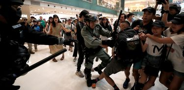 A man scuffles with a police officer as shoppers and anti-government protesters gather at New Town Plaza in Sha Tin, Hong Kong, China November 3, 2019. REUTERS/Shannon Stapleton