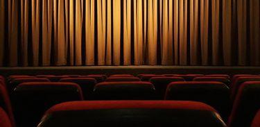 Palco de tetro com cortinas fechadas vistas a partir da plateia