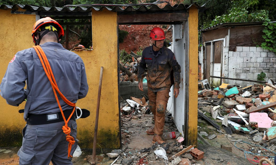Firefighters dig for victims of a mudslide, where five people died and four remain missing according to the fire department, in Morro do Macaco Molhado (wet monkey hill) in Guaruja