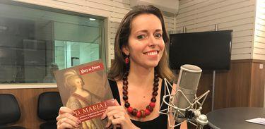 """Apresentadora Isabela Azevedo com o livro """"Dona Maria I"""", da historiadora Mary del Priore"""