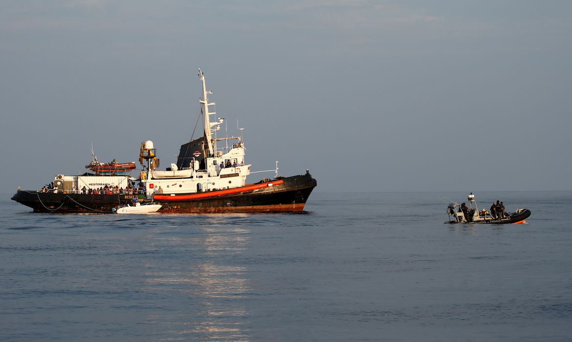 A rigid-hulled inflatable boat (RHIB) of the Italian Finance Police patrols near the Mare Jonio, operated by Italian charity Mediterranea Saving Humans, and the German NGO Sea-Eye migrant rescue ship 'Alan Kurdi' (unseen) in international waters