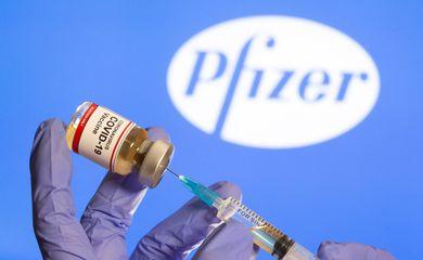 Mulher segura frasco rotulado como de vacina contra Covid-19 em frente a logo da Pfizer em foto de ilustração