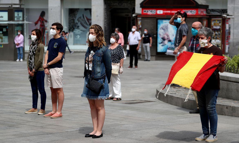 Pessoas com máscaras de proteção durante minuto de silêncio em homenagem às vítimas de Covid-19 em Madri
