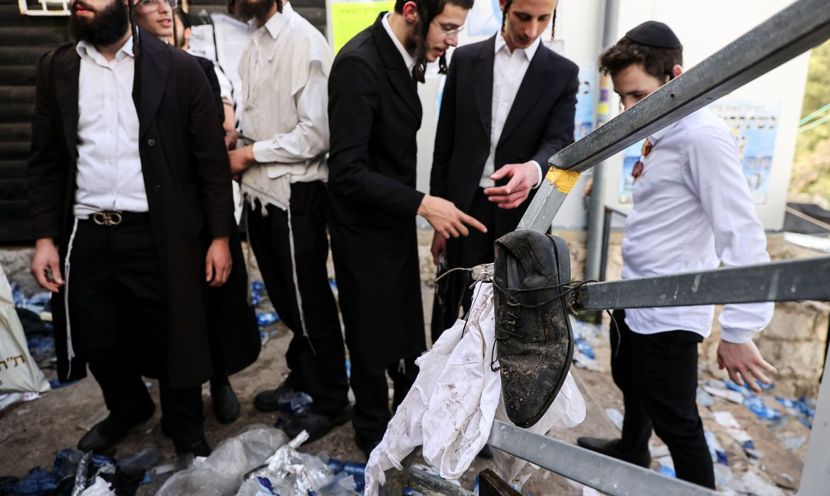 Ultra Orthodox Jews stand next to left over belongings on Mount Meron