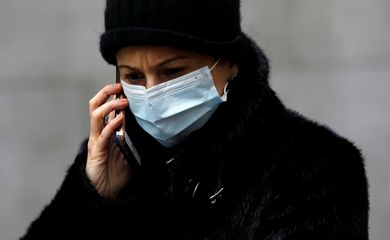 FILE PHOTO: A woman in a surgical mask uses her cellphone after more cases of coronavirus were confirmed in Manhattan, New York City, New York