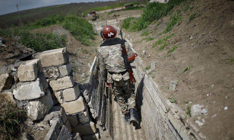 Soldados armênios étnicos caminham em uma trincheira em sua posição perto da fronteira de Nagorno-Karabakh