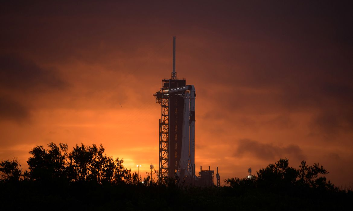 The sun sets behind a SpaceX Falcon 9 rocket with the company's Crew Dragon spacecraft onboard