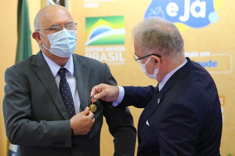 O ministro da Educação, Milton Ribeiro, recebe do ministro da Saúde, Marcelo Queiroga, a medalha do Mérito Oswaldo Cruz, durante a cerimônia de lançamento da Campanha Nacional para Prevenção da Obesidade Infantil