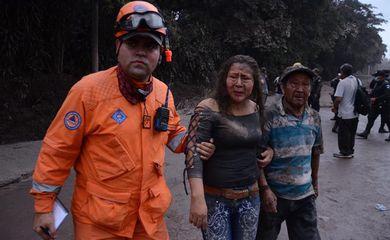 Trabalhador ajuda no resgate de moradores atingidos pela erupção do Vulcão Fogo