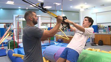 Sala de ginástica. Um rapaz com as mãos nos puxadores de uma fita de treinamento suspenso e o corpo inclinado para trás. De frente para ele, um educador físico com a mão direita na extremidade da fita.