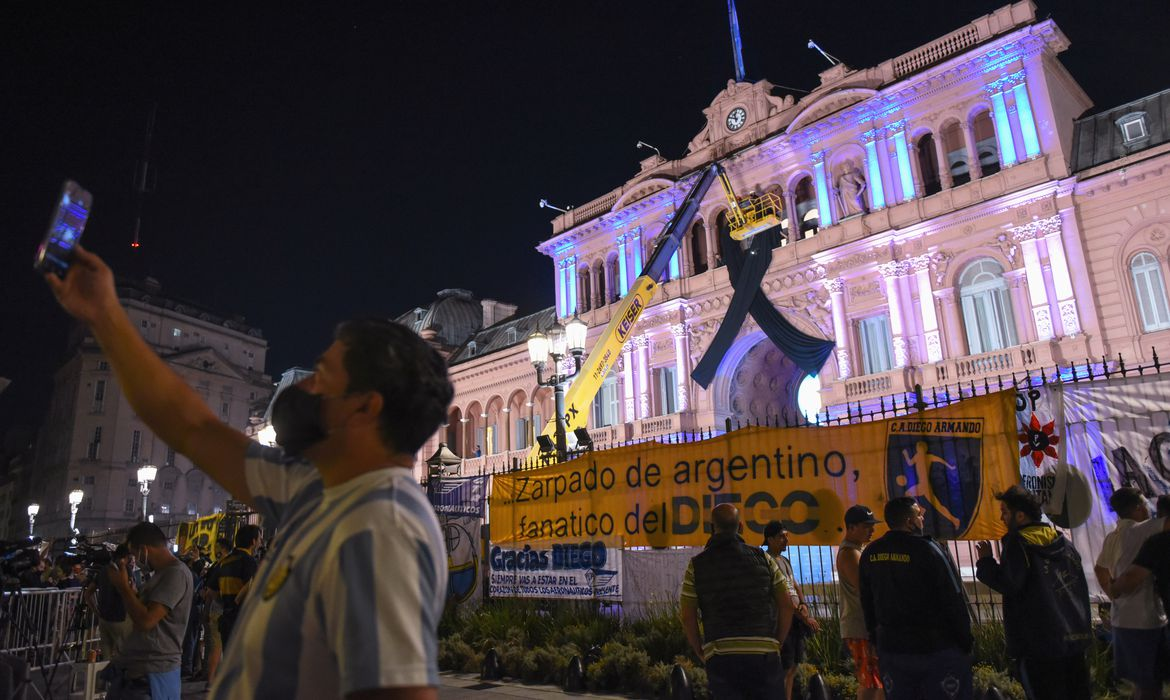 People gather outside the Casa Rosada presidential palace ahead of the wake of soccer legend Diego Maradona, in Buenos Aires