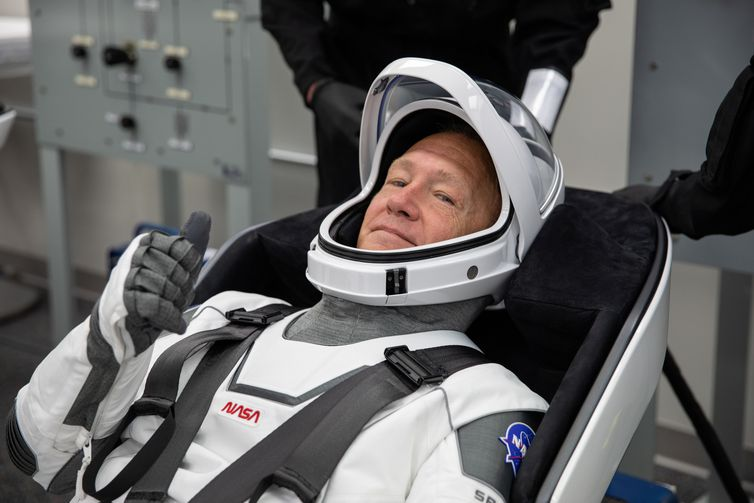 NASA astronaut Douglas Hurley rehearses putting on his SpaceX spacesuit in the Astronaut Crew Quarters