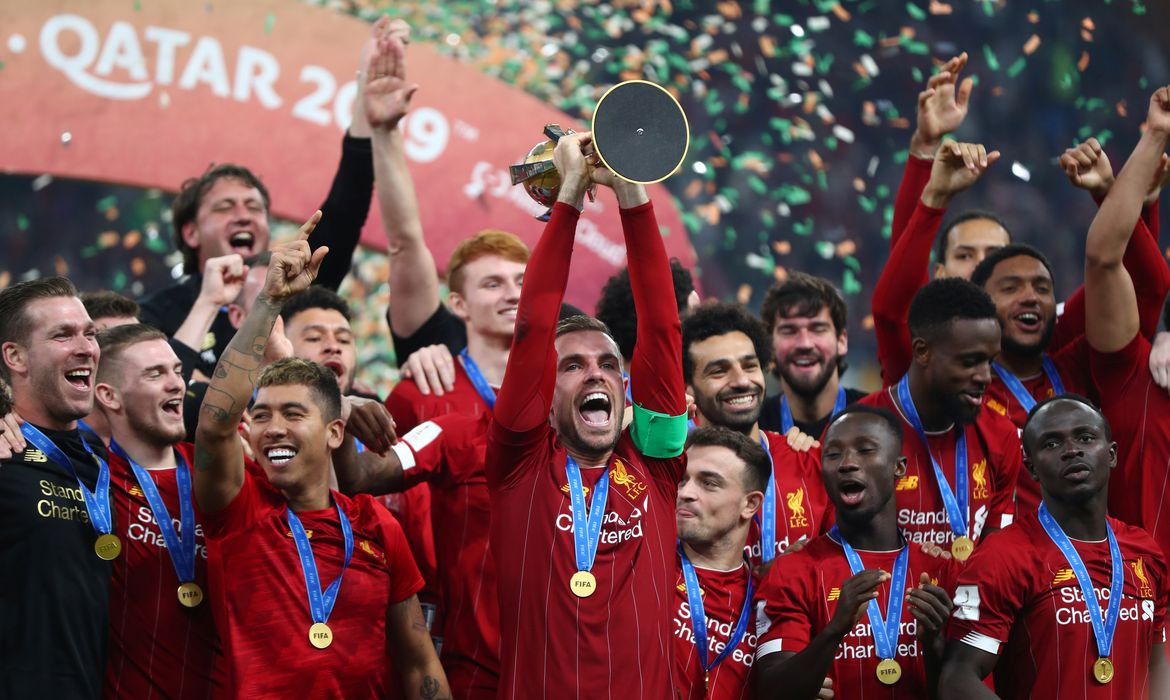 Soccer Football - Club World Cup - Final - Liverpool v Flamengo - Khalifa International Stadium, Doha, Qatar - December 21, 2019  Liverpool's Jordan Henderson and teammates celebrate winning the Club World Cup with the trophy    REUTERS/Ibraheem