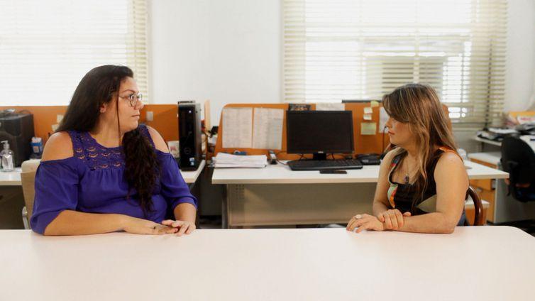 Sala com computadores. Sentadas a uma mesa, Kamilla e Fernanda de frente uma para outra.