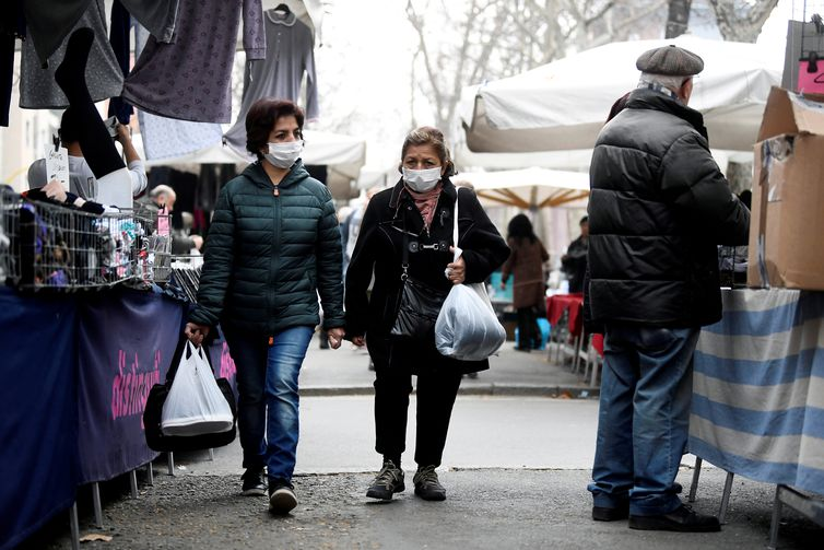 Women in face masks walk at the local market in Milan