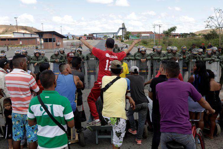 Pessoas esperando para atravessar para a Venezuela em frente aos guardas nacionais venezuelanos na fronteira entre a Venezuela e o Brasil em Pacaraima.