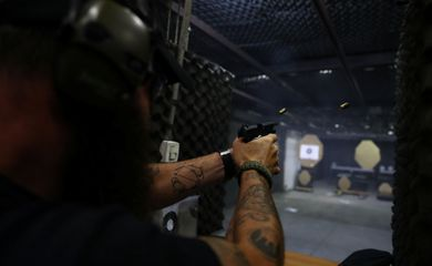 Joao Bercle, instructor of the Colt 45 shooting club, fires a gun, in Rio de Janeiro