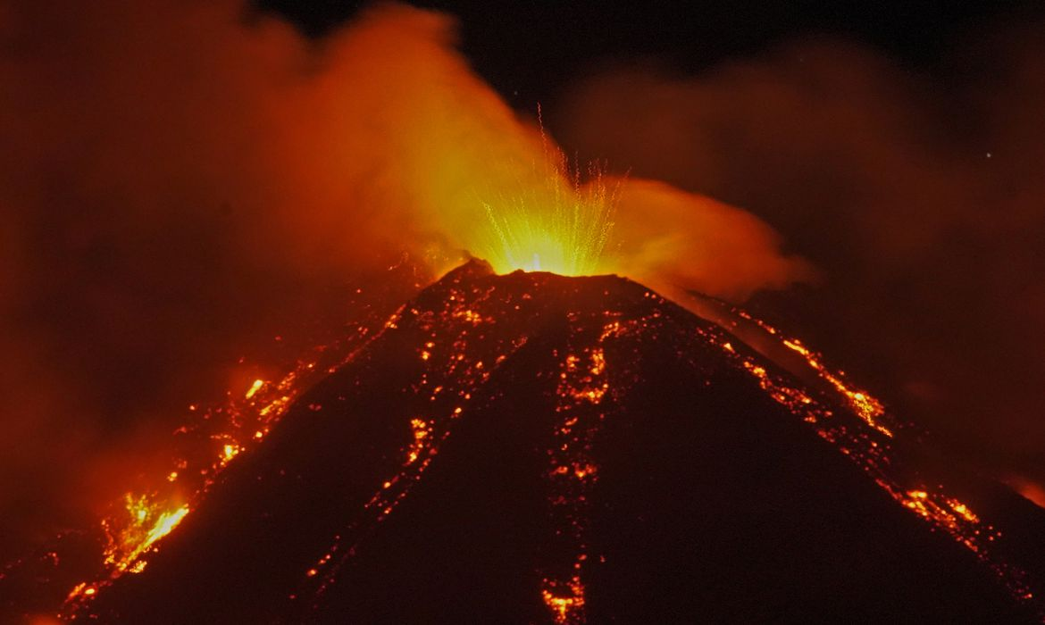 An eruption from Mount Etna lights up the sky during the night, seen from Fornazzo