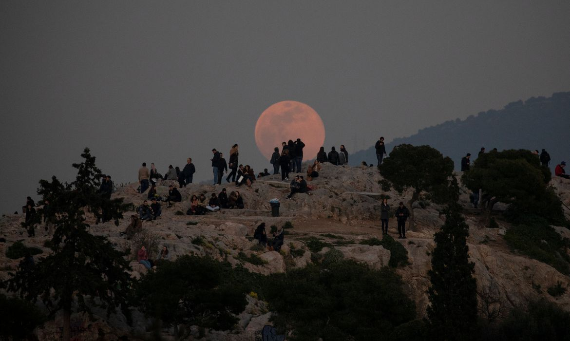 A super snow moon rises as people visit the Areios Pagos hill at the archaeological site of the Acropolis in Athens, Greece February 19, 2019.