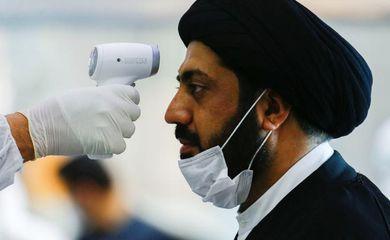 Membro de equipe médica checa temperatura de clérigo em meio a preocupações com aumento de infecções por coronavírus no Irã