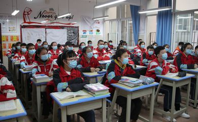 Junior high students wearing face masks attend a class on their first day of returning to school following an outbreak of the novel coronavirus, in Guiyang, Guizhou