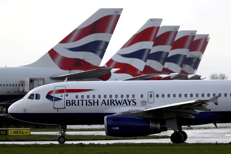FILE PHOTO: A British Airways plane taxis past tail fins of parked aircraft at Heathrow Airport in London