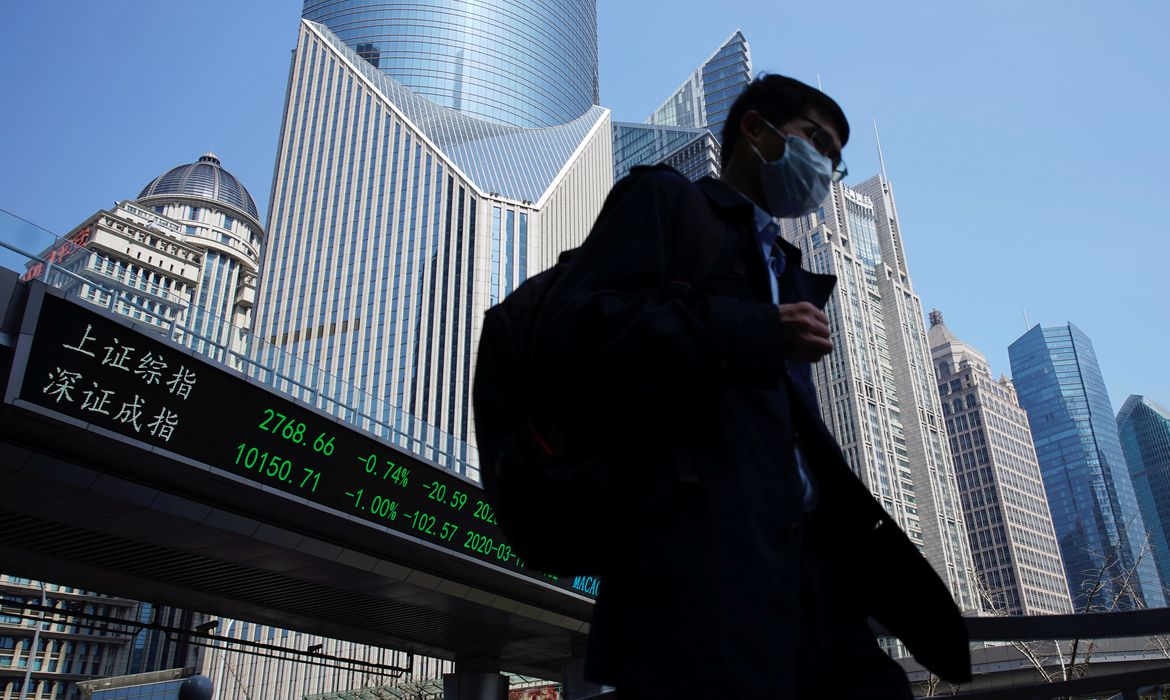 Pedestrian wearing a face mask walks near an overpass with an electronic board showing stock information in Shanghai