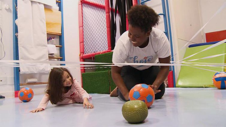 Em uma sala, professora e aluna estão agachadas no chão rindo, em meio a exercícios para desenvolver psicomotricidade