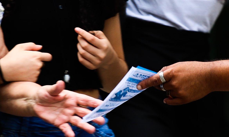 Trabalhador informal distribui panfleto na Avenida Paulista.