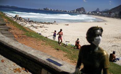 Uma estátua é vista com uma máscara facial enquanto as pessoas aproveitam o clima na praia do Leme, após o surto da doença por coronavírus (COVID-19), no Rio de Janeiro, Brasil, em 29 de abril de 2020. Foto tirada em 29 de abril de 2020.