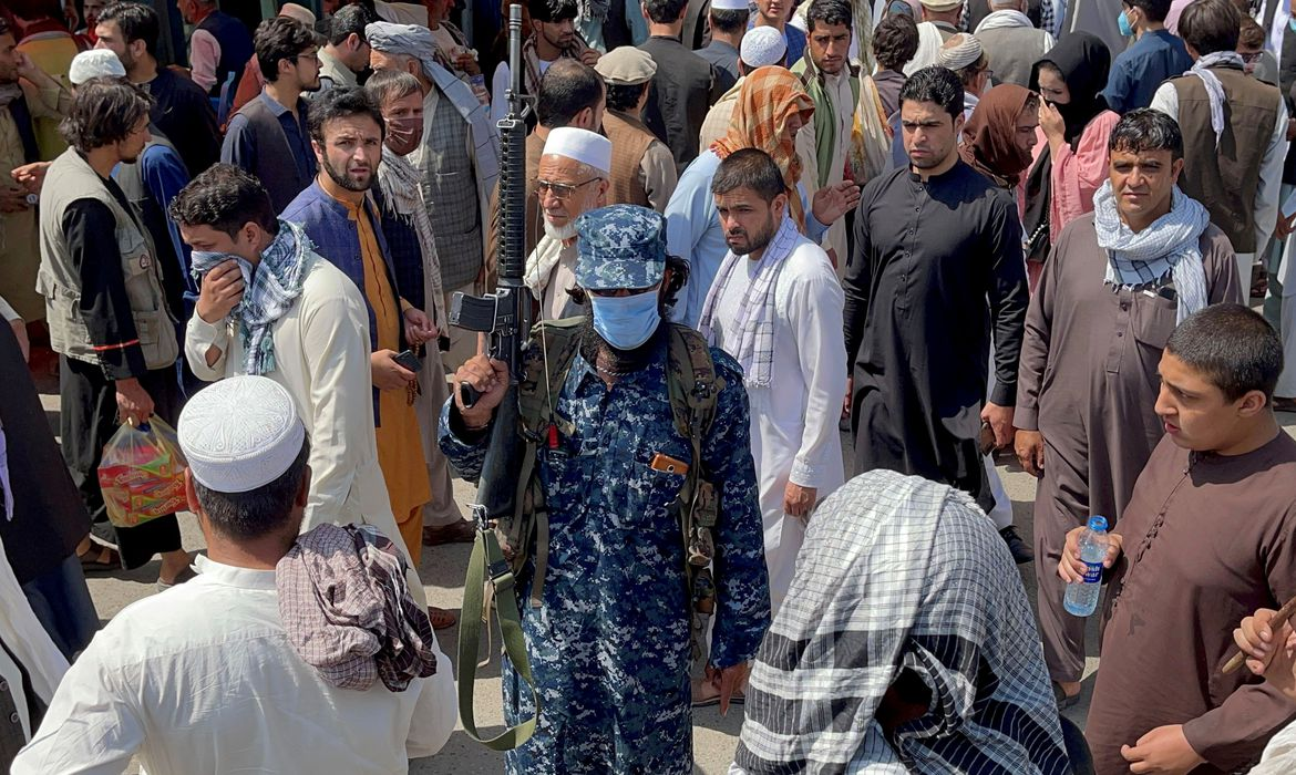 FILE PHOTO: Member of Taliban security forces stands guard among crowds of people in a street in Kabul