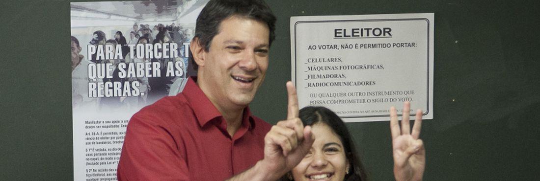 O candidato à prefeitura pelo PT, Fernando Haddad, vota junto de sua filha Carolina no segundo turno das eleições municipais de 2012.
