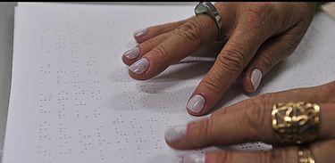 Close em mãos de pessoa que ler texto escrito em braile