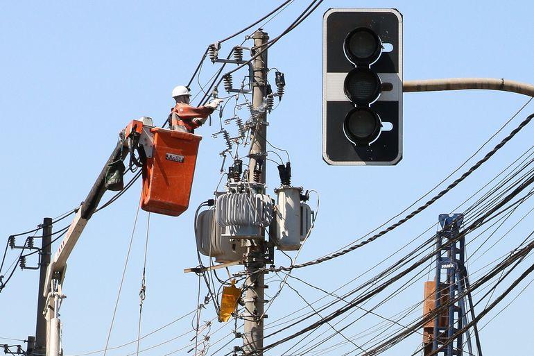 Funcionários da Enel fazem manutenção em poste de energia elétrica no bairro de Pinheiros.