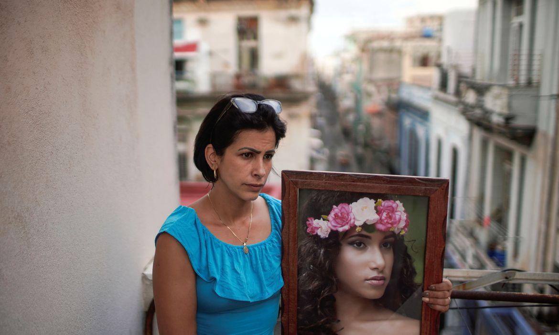 Heissy Celaya posa com retrato da filha Amanda Celaya, que foi detida durante protestos em Havana