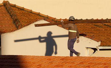 Operários reformam telhado de imóvel em obras no Centro do Rio.