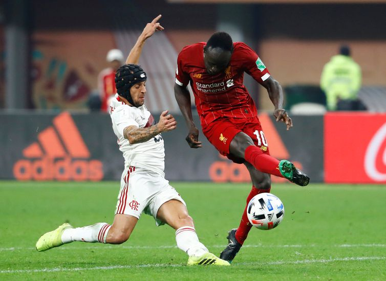Soccer Football - Club World Cup - Final - Liverpool v Flamengo - Khalifa International Stadium, Doha, Qatar - December 21, 2019  Liverpool's Sadio Mane is fouled by Flamengo's Rafinha before the referee's decision is overturned following a