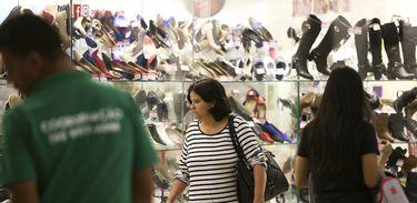 Pessoas caminhando em frente a vitrine de loja de sapatos em shopping