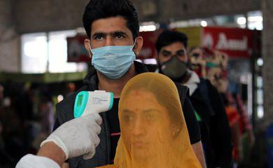 Um trabalhador de saúde em equipamentos de proteção individual (EPI) verifica a temperatura dos passageiros em meio à propagação da doença coronavírus (COVID-19), em uma estação ferroviária em Mumbai, Índia, 19 de dezembro de 2020. REUTERS / Fr
