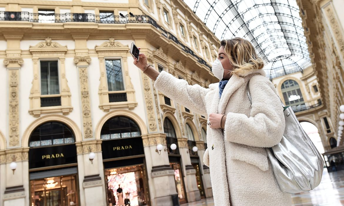 A woman wearing a protective face mask takes a selfie in Galleria Vittorio Emanuele II after a decree orders for the whole of Italy to be on lockdown in an unprecedented clampdown aimed at beating the coronavirus, in Milan