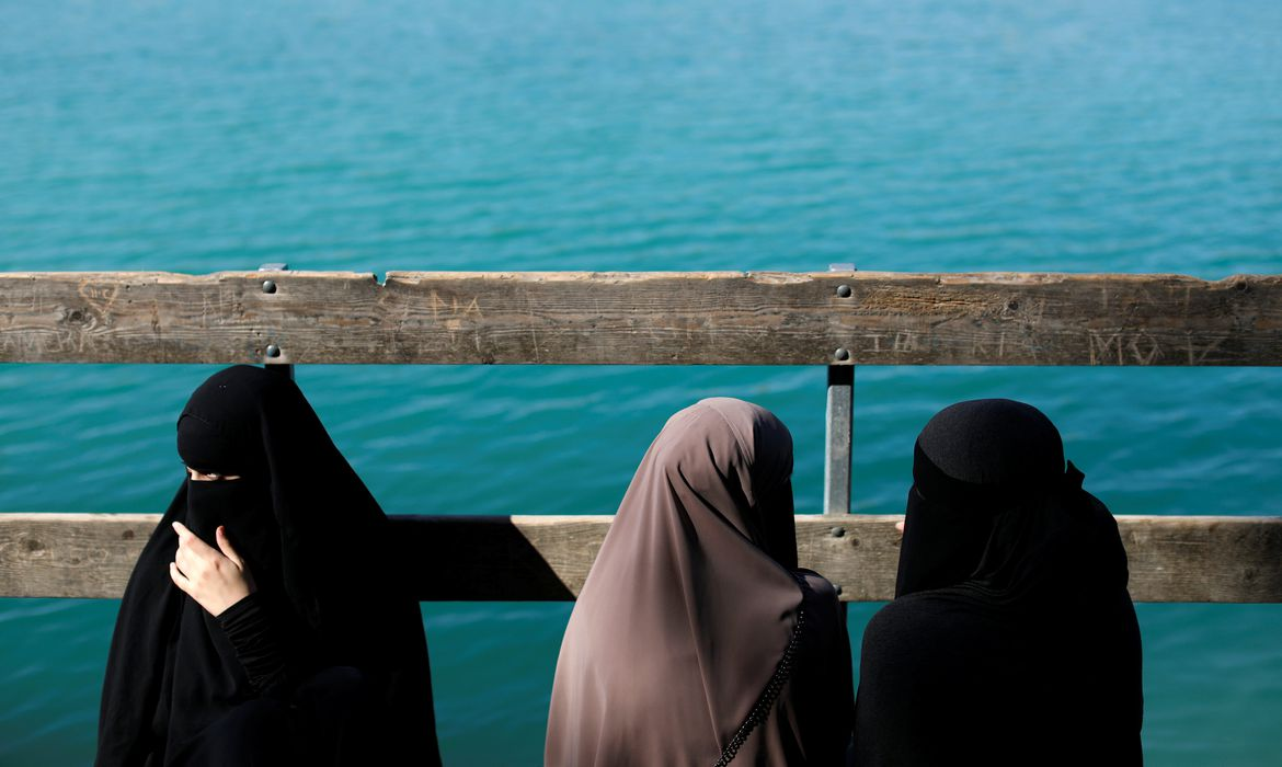 Alaa (L), 21, Amina (C), 24, and Nayab, 18, sit on a dock during a visit to Karlstrup Kalkgrav, a lake near Karlstrup located outside Copenhagen, Denmark, July 19, 2018.  REUTERS/Andrew Kelly    SEARCH
