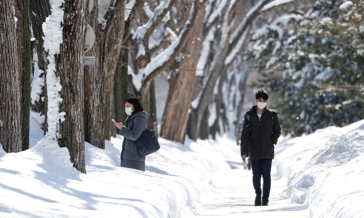 Passersby wearing protective masks walk on a snow-covered street in Sapporo, Hokkaido