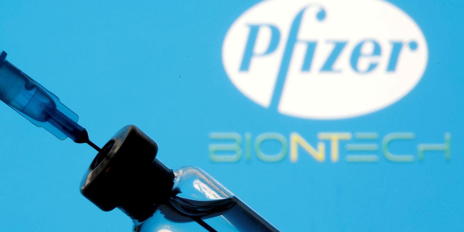 Frasco e seringa em frente aos logos da Pfizer e da BioNTech em foto de ilustração