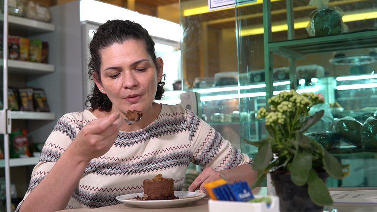 Claudete saboreia o bolo sem glúten.