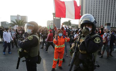 A demonstrator holds a flag during protests following the impeachment of President Martin Vizcarra, in Lima