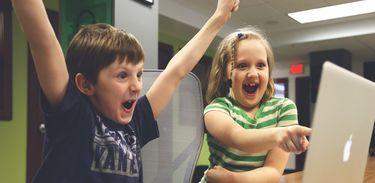 Crianças comemorando ao computador