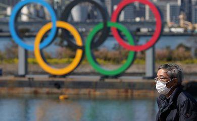 Homem usando máscara de proteção em Tóquio por temor do coronavírus próximo a anéis dos Jogos de Tóquio 2020