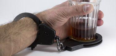 Mão segurando bebida com algema presa no punho