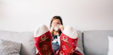 Mulher toma bebida em caneco sentada no sofá e com os pés na mesa. Close nos pés com meias coloridas.